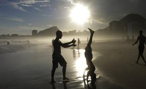 A boy does a headstand at sunset on Copacabana Beach in Rio de Janeiro